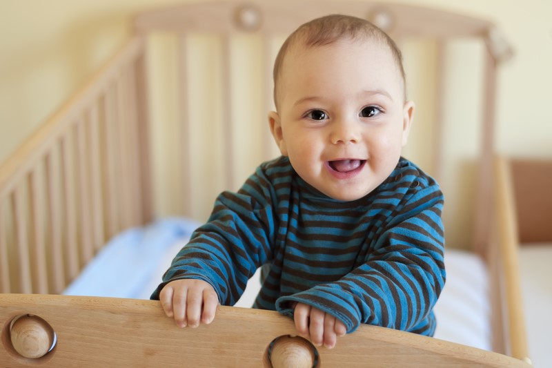 baby smiling in cot