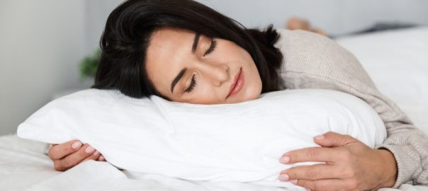 Photo of adult woman sleeping while lying in bed with white linen at home