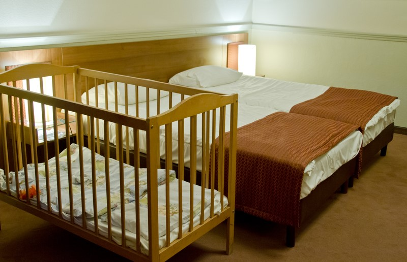 baby cot next to double bed